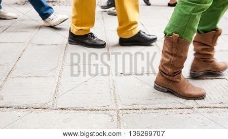 People walking bgy showing legs and differing footwear only on cobbled European street.