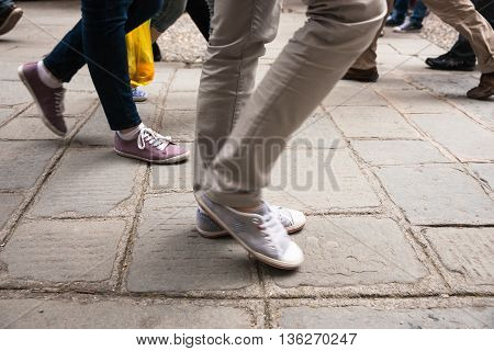 Walking legs on European cobbled street motion blur with focus on pink sandshoe