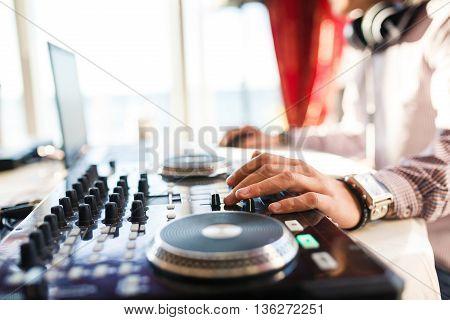 Hand of DJ on the decks close up