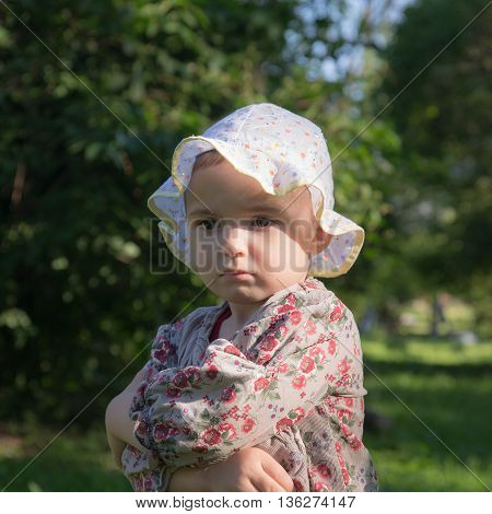 portrait of a pensive little girl in summer