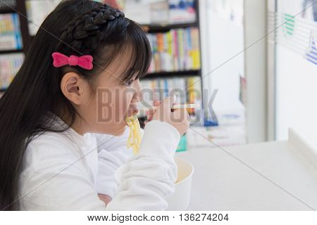 Asian girl eating Spaghetti Carbonara in convenience store