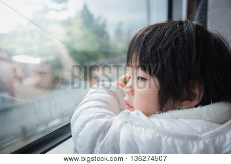 Happy asian child looking out train window outside while it moving. travel