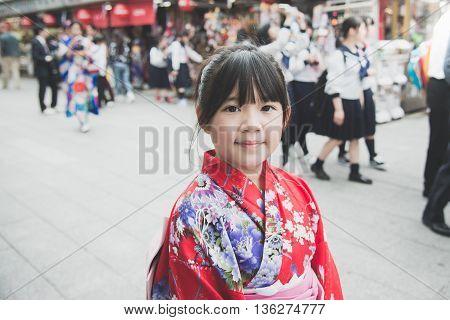 Beautiful Asian girl wearing red kimono walking in the city Asakusa Tokyo Japan.