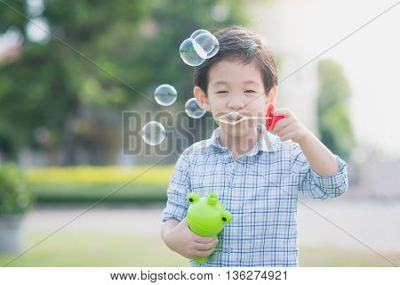 Cute asian child is blowing a soap bubbles outdoor