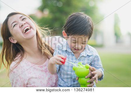 Asian mother and son blowing bubbles outdoors in summer sunshine