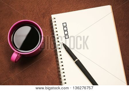 Checklist - text on notebook with a pen and cup of coffee