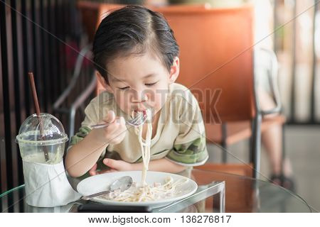 Cute Asian chid eating Spaghetti Carbonara in restaurant