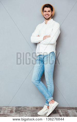 Full length portrait of a handsome man standing with arms folded isolated on a gray background