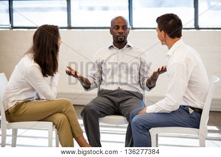 Business people having a discussion while sitting in modern studio