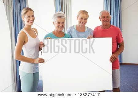 Seniors and fitness instructor holding a blank paper in studio