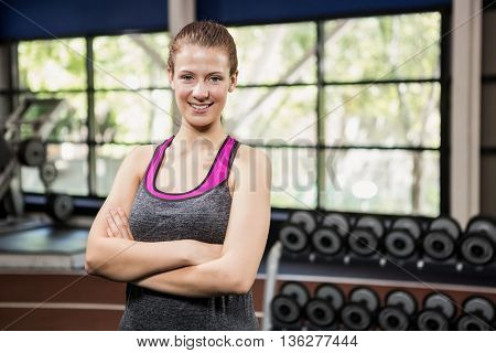 Portrait of beautiful woman standing with arms crossed at gym
