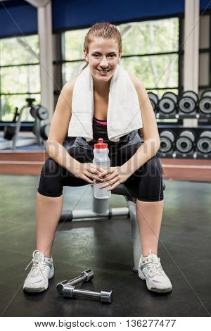 Portrait of woman sitting with a water bottle in gym