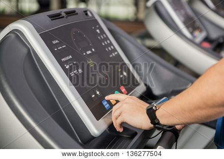 Hand pressing a button on the console display of a treadmill at gym