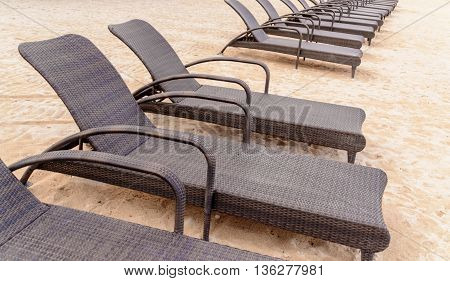 Outdoor recliner chairs lined up on the beach with nobody around.