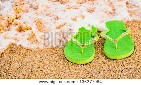 A pair of womens green sandals at the seashore with a wave washing over the top.