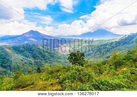 Volcano and mountains scenic photo with clouds and blue sky.