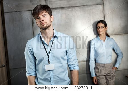Portrait of young businessman, businesswoman standing at background.