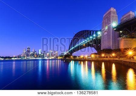 A view of Sydney Harbor Bridge looking towards the city at sunrise.