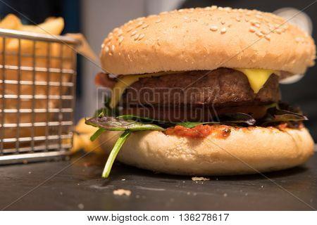 Tasty hamburger served on a black stone