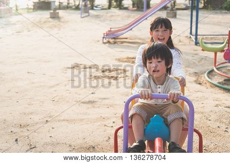 Cute asian children riding seesaw board at the playground under sunlight