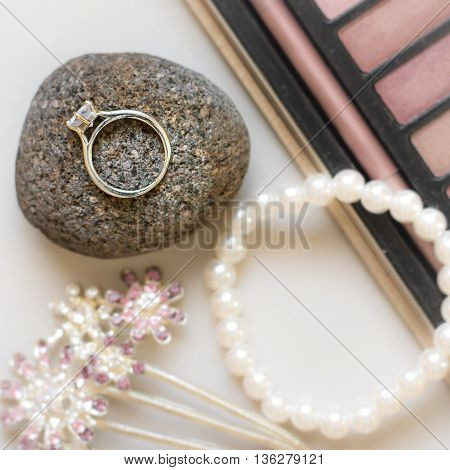 a wedding ring set on stone with other accessories and makeup.