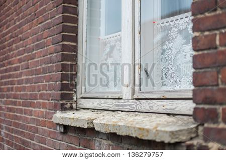 Antique white wooden window frames, lace curtains and a stone windowsill on a dark red brick house