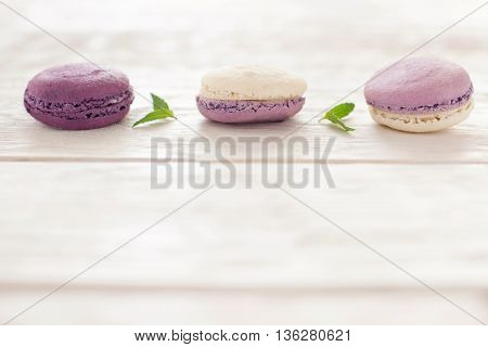 Macaroons line on wooden background copyspace. Three purple french macaroons horizontal line at the top of image. Ratafia on white wooden background