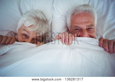 Portrait of happy senior couple hiding under blanket while lying on bed