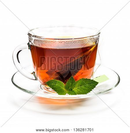 Transparent cup of black tea with tea bag and mint leaves isolated on white background