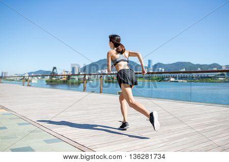 Back view of woman running in seaside boardwalk