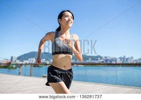 Woman running in seaside boardwalk