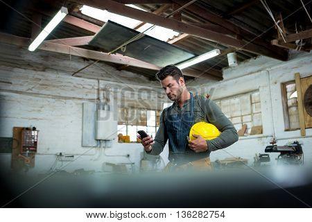 Carpenter using phone on his workshop