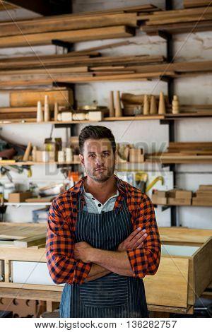 Carpenter crossing arms in his workshop