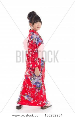 Beautiful Asian girl in red kimono standing on white background isolated