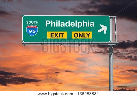 Philadelphia exit only highway sign with sunrise sky.