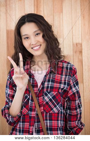 Smiling hipster showing peace on wooden background