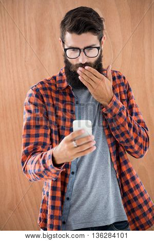 Shocked hipster with smartphone on wooden background