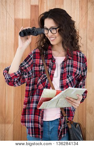 Hipster with binoculars and map on wooden background
