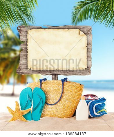 Summer concept with empty wooden board and blank paper for message. Tropical sandy beach on background.