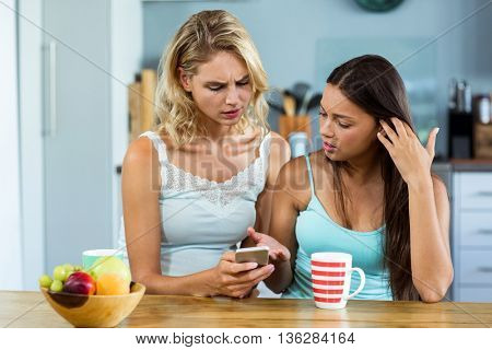Female friends looking into mobile phone in kitchen at home