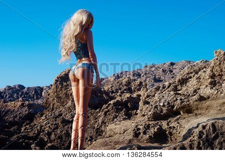 Beautiful sensual blonde in a greek sandals at the seashore. Summer travel fashion photo