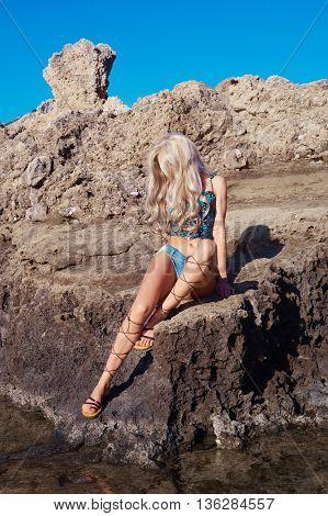 Beautiful sensual blonde in a greek sandals at the seashore. Summer travel fashion photo