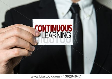 Business man holding a card with the text: Continuous Learning