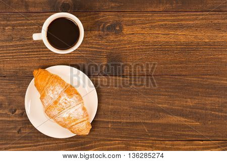 Coffee cup with croissant for breakfast on a dark wooden table top view