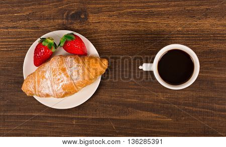 Continental breakfast with croissant coffees and fresh strawberries.