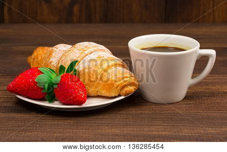 Continental breakfast with croissant, coffees and fresh strawberries.