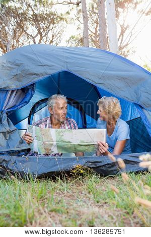 Mature couple studying map on camp site