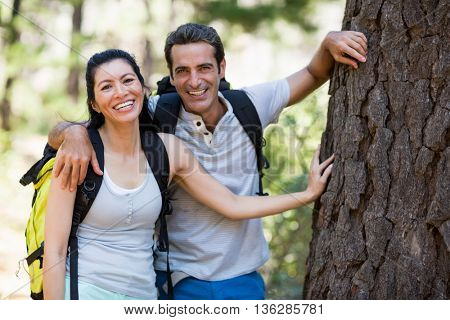 Couple smiling and resting against a tree on the wood