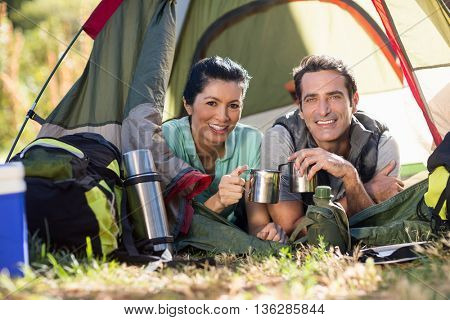 Couple laying and holding cup on a tent
