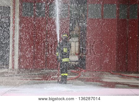 Brave Fireman During The Fire Drill With The Hose Foam